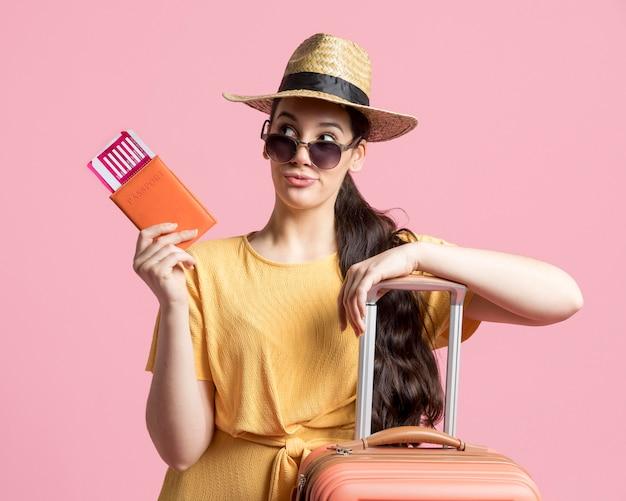 Mulher com óculos de sol, segurando seu passaporte