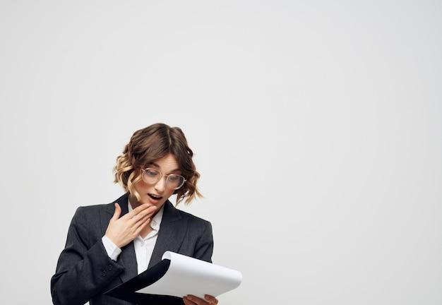 Mulher com óculos, documentos na mão, trabalho profissional