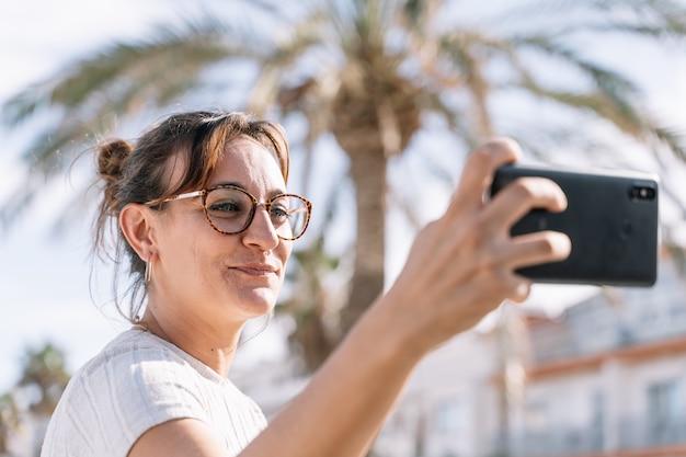 Mulher com óculos e cabelo amarrado fazendo um selfie