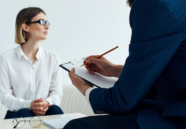 Mulher com óculos e homens com documentos à mesa dentro de casa