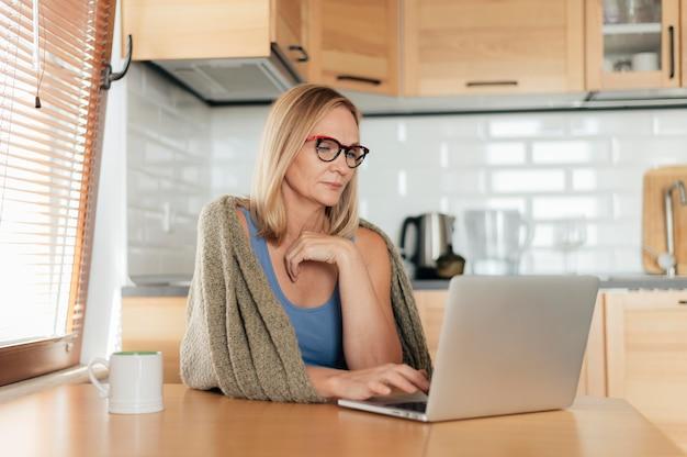 Mulher com óculos e laptop durante a quarentena