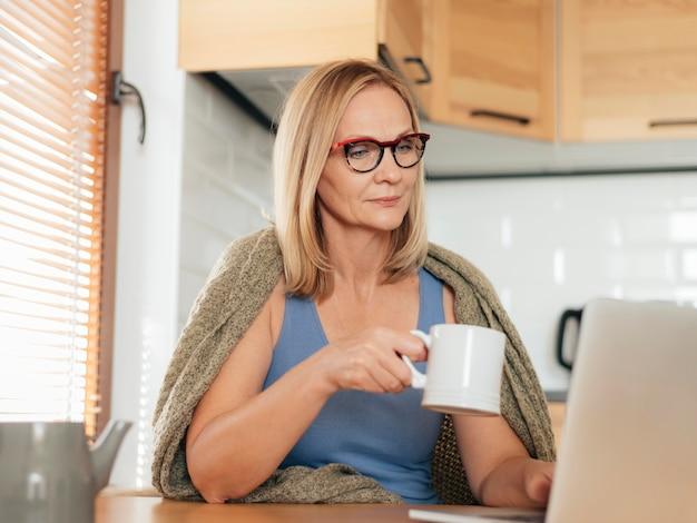 Mulher com óculos e laptop durante quarentena em casa