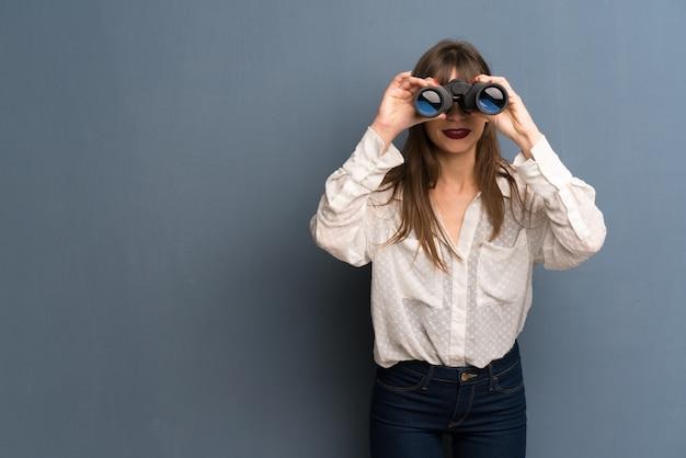 Mulher com óculos e olhando ao longe com binóculos