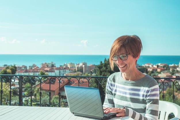 Mulher com óculos e roupas casuais, trabalhando no laptop ao ar livre no terraço