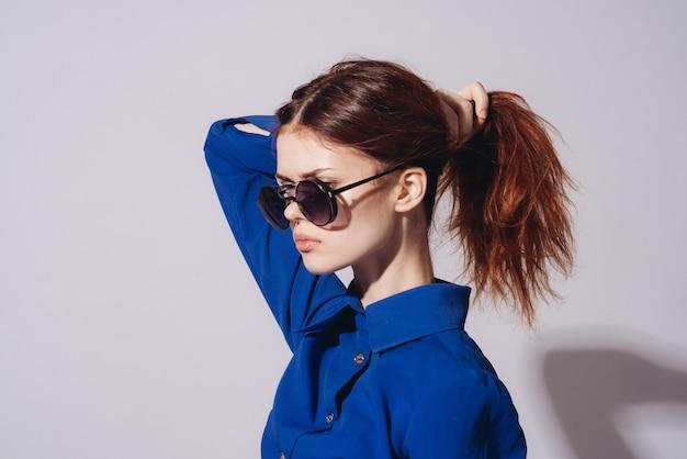 Mulher com óculos escuros posando contra a parede cinza