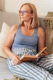 Mulher com óculos lendo um livro em casa no sofá durante a quarentena