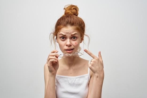 Mulher com óculos mostra um dedo para uma espinha vermelha no rosto acne problemas de saúde.