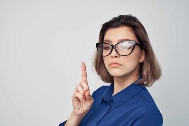 Mulher com óculos na camisa azul posando de moda elegante