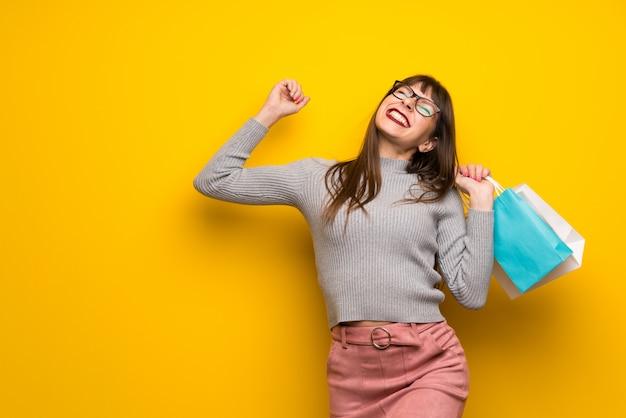 Mulher, com, óculos, sobre, parede amarela, segurando, um, lotes, de, bolsas para compras, em, posição vitória