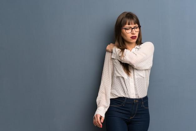 Mulher com óculos, sofrendo de dor no ombro por ter feito um esforço