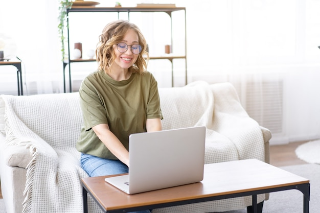 Mulher com óculos usa laptop digitando teclado sentado no sofá janela grande fundo interior da casa mulher autônoma trabalhando em casa