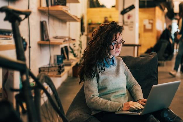 Mulher com óculos usando laptop no interior moderno.