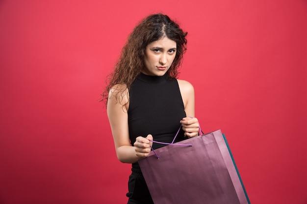 Mulher com olhar complicado e muitas compras em fundo vermelho. foto de alta qualidade