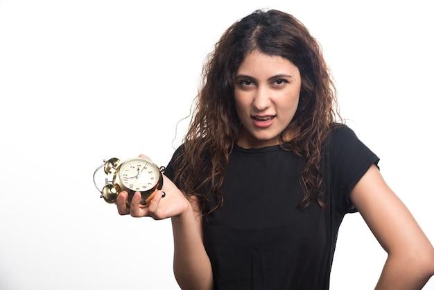Mulher com olhar complicado segurando o relógio no fundo branco