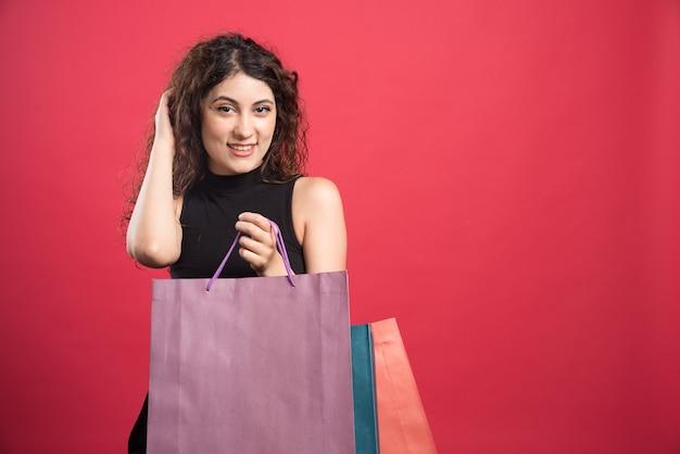 Mulher com olhar complicado segurando sacolas em fundo vermelho