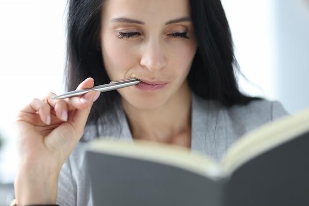 Mulher com olhos astutos olha para o diário. mulheres de sucesso no conceito de negócio