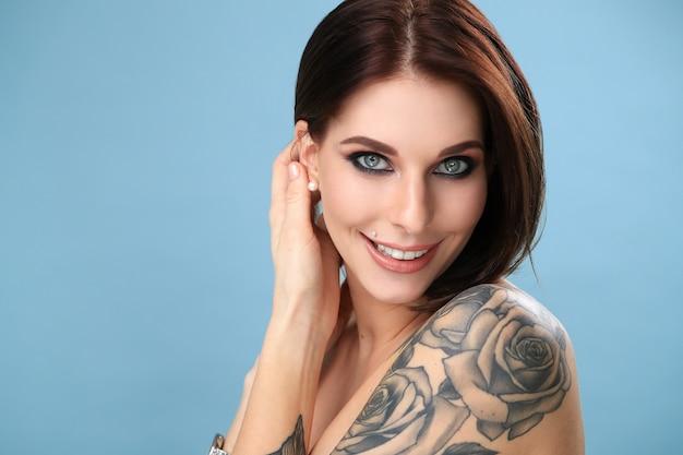 Mulher com olhos azuis e rosa tatuagem sorrindo