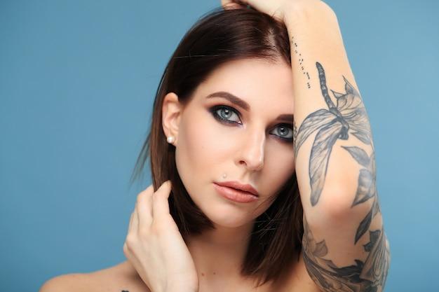 Mulher com olhos azuis e tatuagem de borboleta
