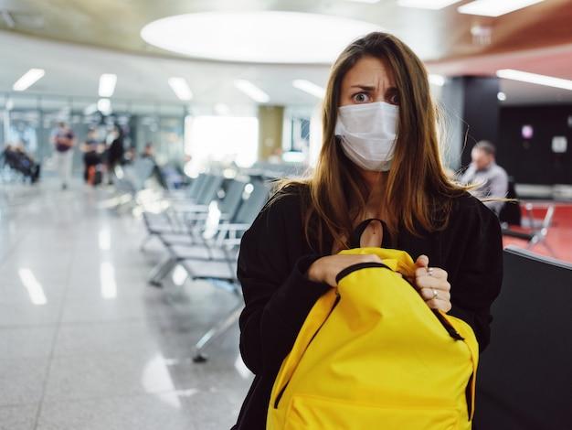 Mulher com olhos bem abertos, máscara médica, mochila amarela, aeroporto
