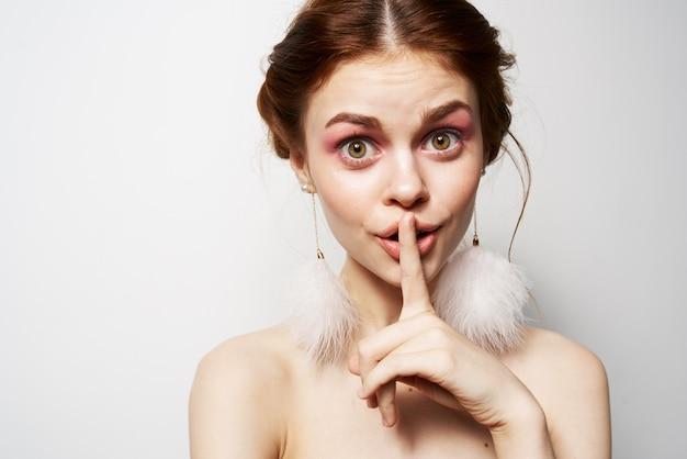 Mulher com ombros nus brincos cosméticos joias closeup