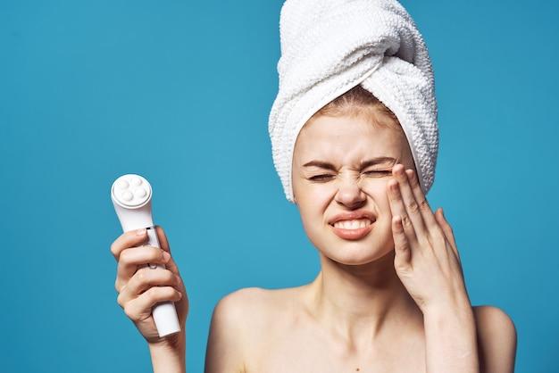 Mulher com ombros nus com uma toalha na cabeça massageador facial