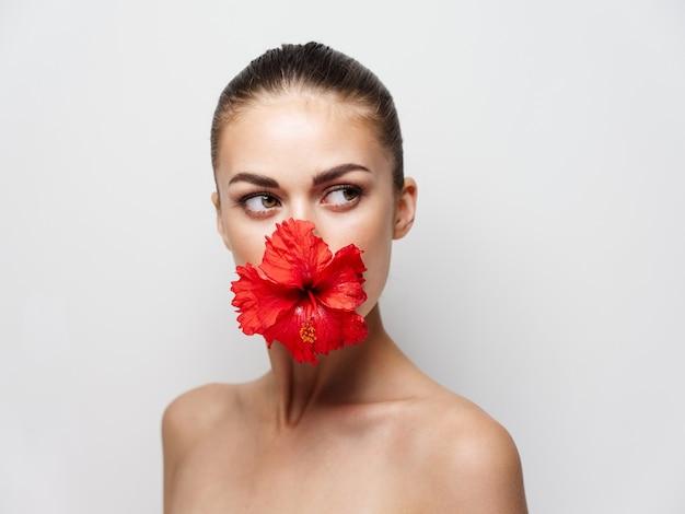 Mulher com ombros nus decoração de flor vermelha vista recortada