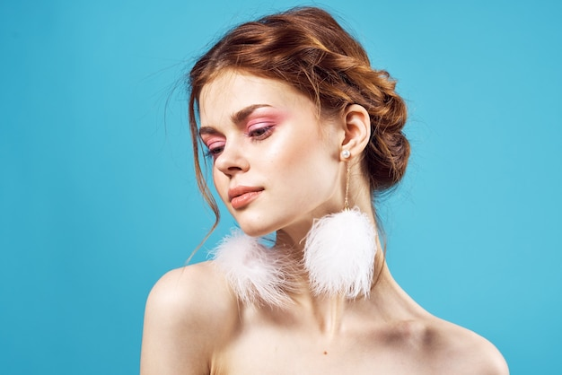 Mulher com ombros nus e brincos fofos, cosméticos divertidos da moda