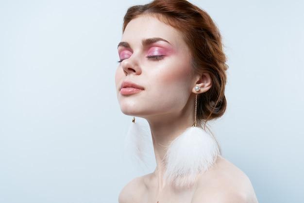 Mulher com ombros nus e joias com maquiagem brilhante e brincos fofos