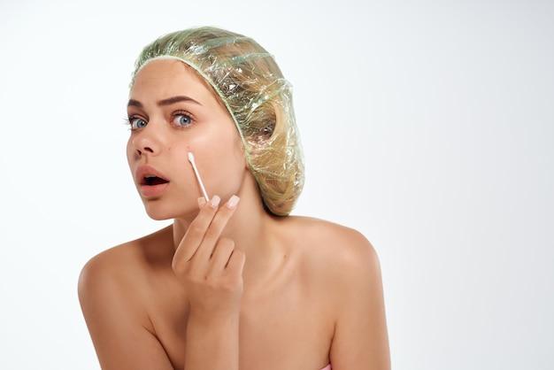 Mulher com ombros nus enxugando o rosto com um cotonete de problemas de pele