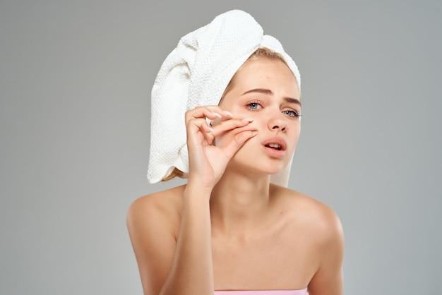 Mulher com ombros nus espremendo espinhas na toalha do rosto na cabeça com luz de fundo