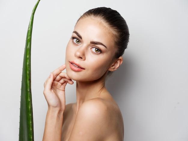 Mulher com ombros nus, folha de aloe vera, pele clara, vista recortada