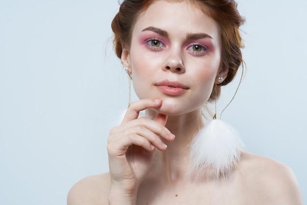 Mulher com ombros nus jóias maquiagem brilhante frescor recortado vista de fundo isolado. foto de alta qualidade