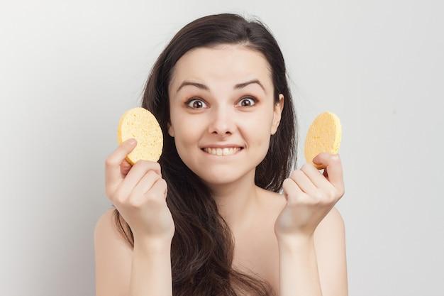 Mulher com ombros nus limpa a pele de cosméticos com uma esponja.