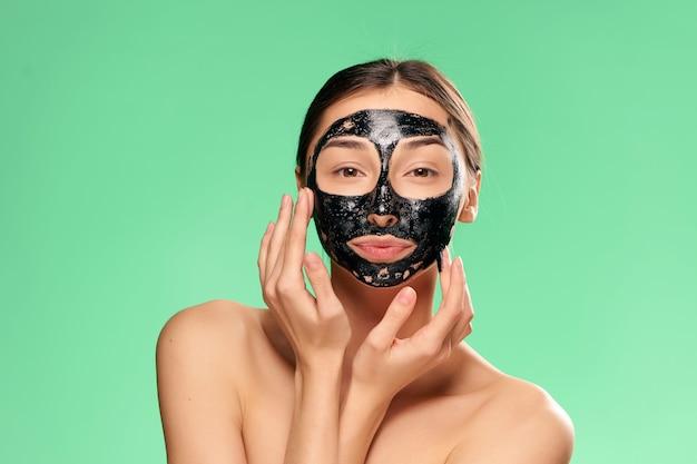 Mulher com ombros nus máscara facial preta cuidados com a pele