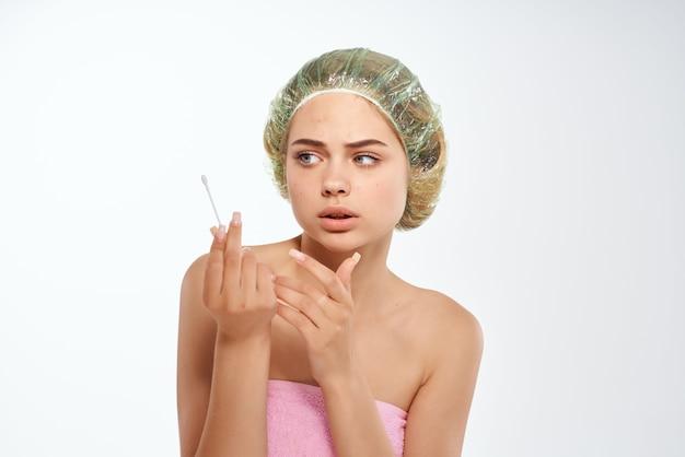 Mulher com ombros nus, pele limpa, toalha rosa, cuidados para o rosto