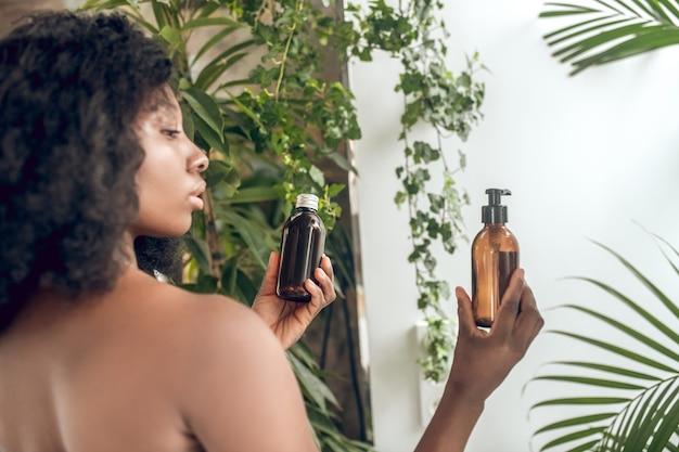 Mulher com ombros nus segurando produtos de beleza