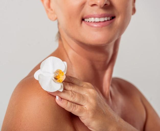 Mulher com ombros nus, segurando uma flor de orquídea