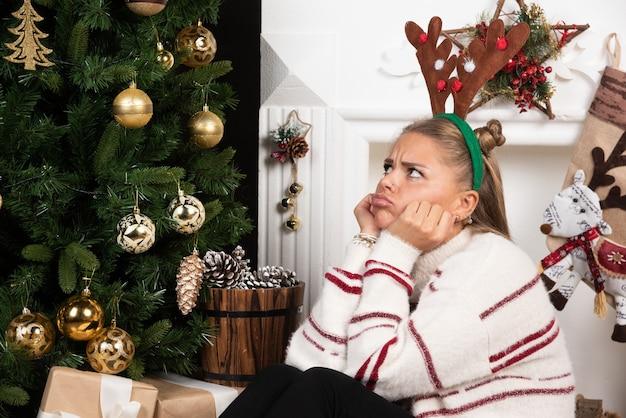 Mulher com orelhas de veado, sentada no tapete e olhando pensativa.