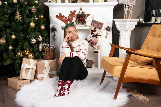 Mulher com orelhas de veado, sentada no tapete enquanto pensa.
