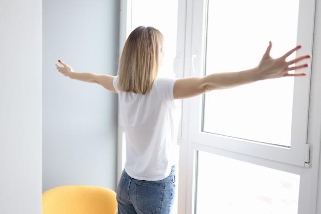 Mulher com os braços abertos e em pé perto da janela