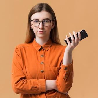 Mulher com os braços cruzados segurando o celular