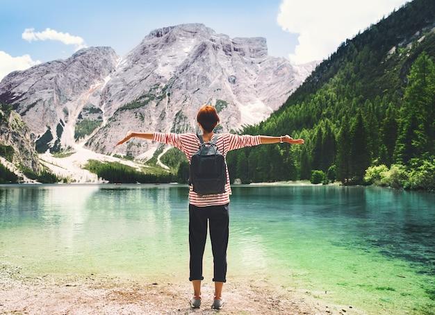 Mulher com os braços erguidos, olhando para o lago braies com montanhas ao fundo
