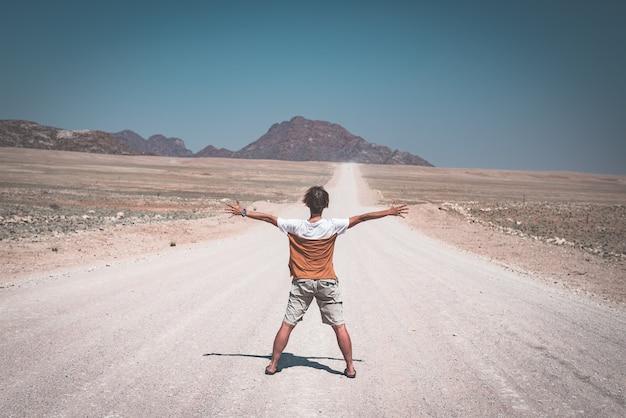 Mulher com os braços estendidos em pé na estrada de cascalho, cruzando o deserto do namibe, no namib naukluft national park, principal destino de viagem na namíbia, áfrica. vista traseira, imagem enfraquecida.