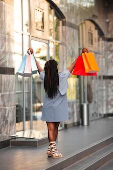 Mulher com os braços levantados com sacolas de compras