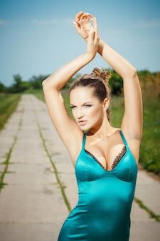 Mulher com os braços levantados em uma estrada