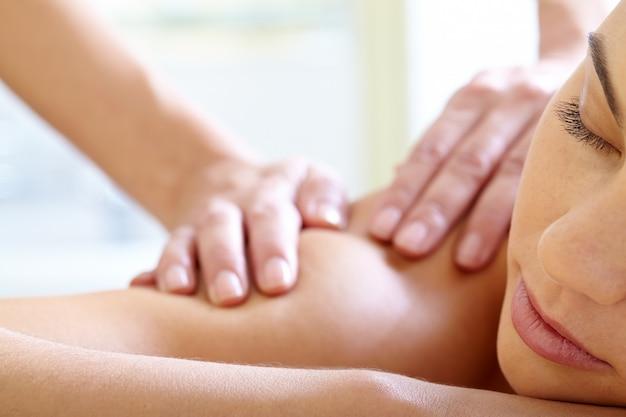 Mulher com os olhos fechados apreciando a massagem
