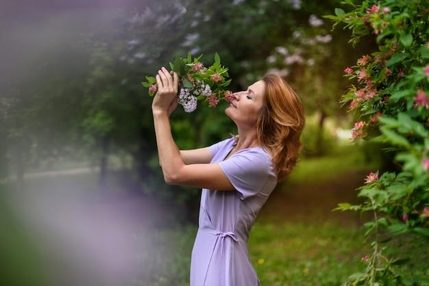 Mulher com os olhos fechados cheira o buquê de flores no parque de verão