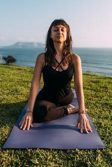 Mulher com os olhos fechados, concentrada em sua rotina de exercícios de ioga, sentada em seu tapete do lado de fora de casa na costa perto do mar
