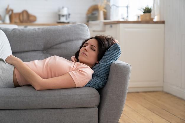 Mulher com os olhos fechados deitada no travesseiro, tentando dormir, em pose desconfortável no sofá em casa