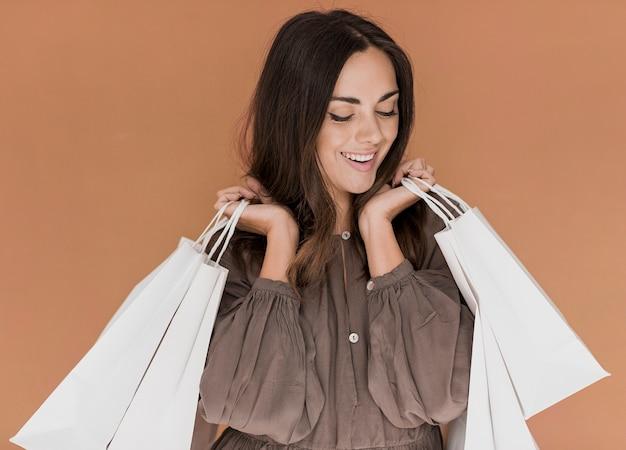 Mulher com os olhos fechados e redes de compras nas duas mãos